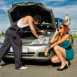 Stock Photo: Mechanic fixing a car on a road