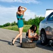 Two girls are fixing a changing a tire. — Stock Photo