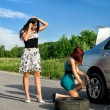 Two women are changing a tire on a road — Stock Photo