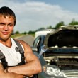 Portrait of a hadsome mechanic with a broken car on background - Stock Photo