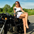 Sexy lady posing on a retro black motorcycle - Stock Photo