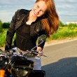 Smiling redhead girl on a motorbike on a road — Stock Photo