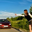 Young pretty girl hitchhiking a red car — Stock Photo