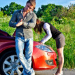 Man is waiting his girlfriend repairs a broken car - Stock Photo