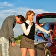Tired man leaning to his gilfriend shoulder near broken car — Stock Photo