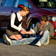 Young girl masures man&amp;#039;s pulse on a road. First aid - Stock Photo