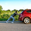 Man and woman pushing a broken car — Foto de Stock