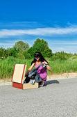 Vrouw op een weg krijgen kleren van koffer. — Stockfoto