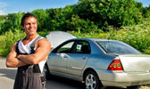 Handsome mechanic on a road near the broken car — Foto Stock