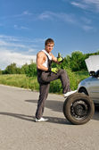 Handsome mechanic with a tire on a road — Stock Photo