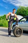 Bello e meccanico in piedi su un pneumatico sulla strada — Foto Stock
