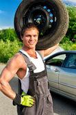 肩上举行一个轮胎一个英俊技工的肖像 — 图库照片