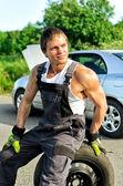 Porträt von gut aussehend mechaniker auf einen reifen auf der straße sitzen. — Stockfoto