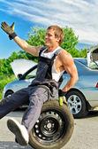 Ritratto di ridere meccanico seduto su un pneumatico su una strada. — Foto Stock