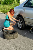 Pretty girl is trying to change a tire on a road — Stock Photo