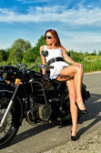 Sexy lady posing on a retro black motorcycle — Stock Photo