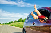 Woman's legs out of the car window. Concept of carefree funny trip. — Stock Photo