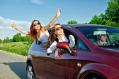 Two pretty happy girls in the car. Concept of carefree roadtrip — Stock Photo