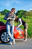 Man is waiting his girlfriend repairs a broken car — Stock Photo