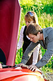 Man and woman are looking at the car engine — Stock Photo