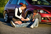 Young girl masures man's pulse on a road. First aid — Stockfoto