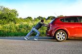 Man and woman pushing a broken car — Stock Photo