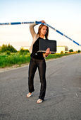 Young criminalist with laptop crossing police tape — Stock Photo