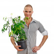 Man holding a pot with plant. Isolated on white background — Stock Photo