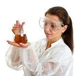 Científico femenino en bata de laboratorio con cristalería química. aislado en blanco. — Foto de Stock