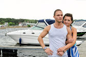 Young couple against pier with boats. — Stock Photo
