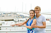Attractive couple against pier with yachts. — Stock Photo