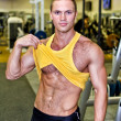 Handsome bodybuilder showing his body in a gym - Stock Photo