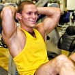 Portrait of handsome bodybuilder doing exercise in fitness club — Stock Photo