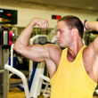 Stock Photo: Handsome bodybuilder showing his muscular arms in gym