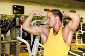 Красивый культурист, показывая его мускулистые руки в тренажерный зал — Стоковое фото