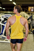 Bodybuilder in a gym from the back — Stock Photo