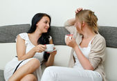 Two women friends chatting over coffee at home — Stock Photo