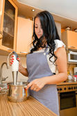 Woman preparing food with a handblender in her kitchen — Stock Photo
