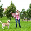 Young woman playing  with puppy - Stock Photo
