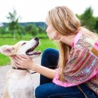 Woman playing with her puppy outdoor - Stock Photo