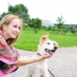 Young woman playing  with puppy outdoor - Stock Photo