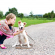 The young woman playing  with puppy outdoor - Stock Photo