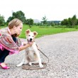 Stock Photo: The young woman playing with puppy outdoor