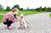 The young woman playing with puppy outdoor — Stock Photo