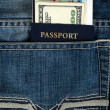 Passport with boarding pass and money in jeans - Stock Photo