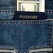Passport with boarding pass and money in jeans — Stock Photo
