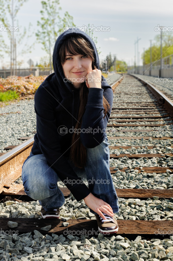 Young girl sitting in the railway in sunny day — Stock Photo #11767441