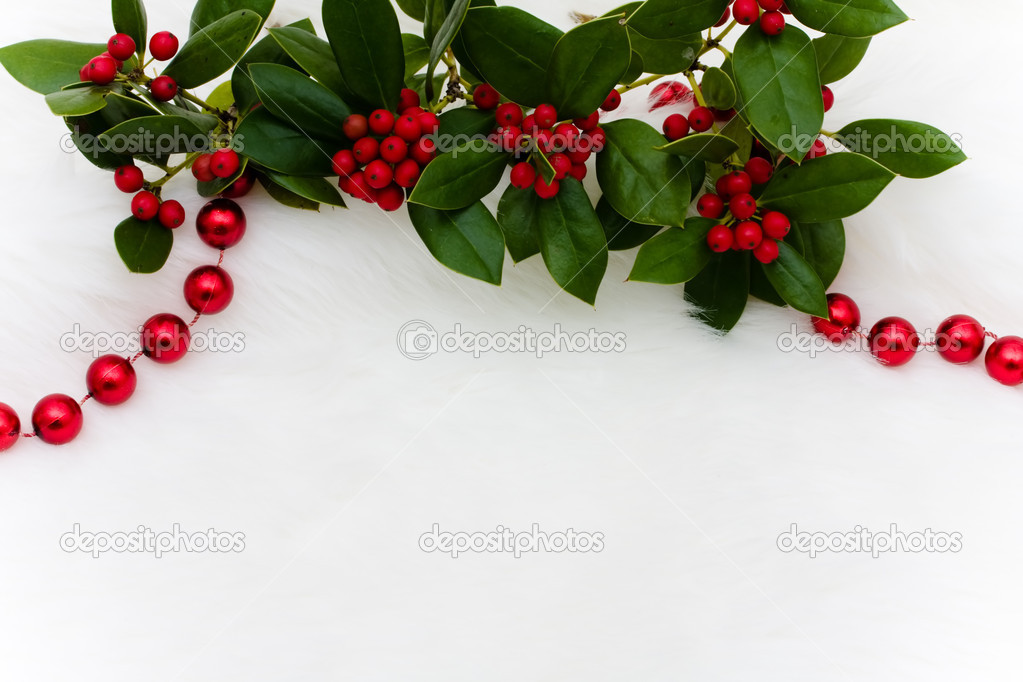Red strung beads and holly and berries on a white fur background, Christmas background  Foto Stock #11843779