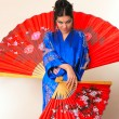 Girl with red asian fan — Stock Photo