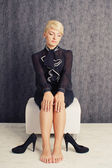 Blonde business woman sitting in black suit with shoes — Stock Photo